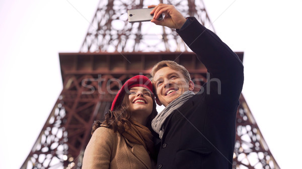 Stock photo: Happy man and woman smiling and posing for selfie in Paris, vacation memories