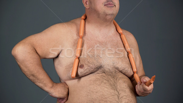 Chubby man eating sausages with appetite, food addiction, risk of diabetes Stock photo © motortion