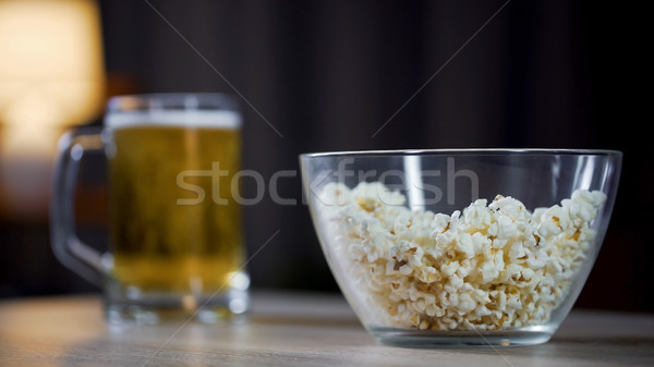 Glass bowl of popcorn and beer standing on table at home, lazy night at home Stock photo © motortion