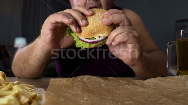Obese person biting big burger, addicted to unhealthy junk food, overeating Stock photo © motortion