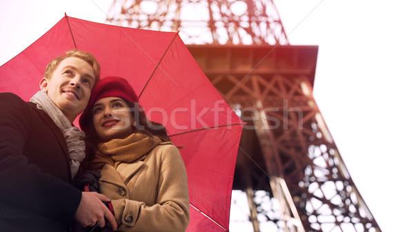 Happy couple in love standing under umbrella in Paris, having romantic vacation Stock photo © motortion