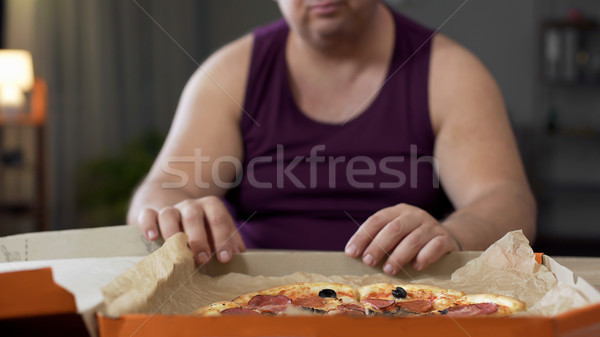 Obese man looking at fatty pizza on table, junk food addiction, overeating Stock photo © motortion