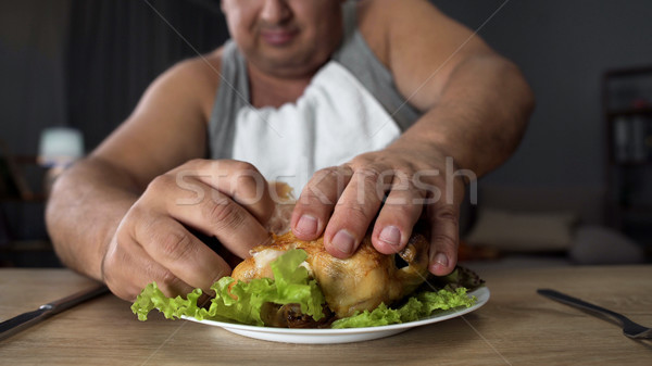 Bad mannered man tearing greasy fried chicken with fingers, fatty food addiction Stock photo © motortion