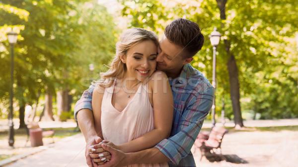 Handsome boyfriend hugging his beautiful girlfriend, romantic date in park Stock photo © motortion