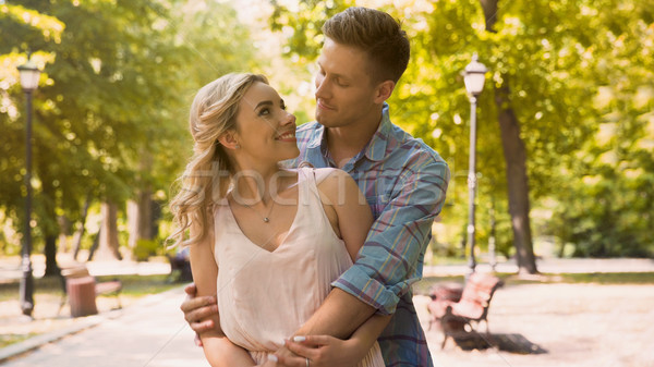 Cute guy and girl looking at each other with love tenderly, cuddling in park Stock photo © motortion