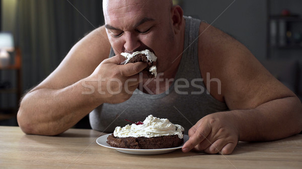 Messy obese man greedily eating cake with whipped cream, addiction to sweets Stock photo © motortion
