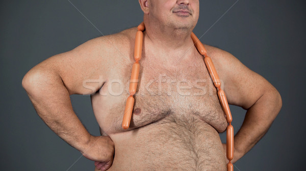 Fat man with sausages round his neck, poor quality nutrition, obesity problem Stock photo © motortion