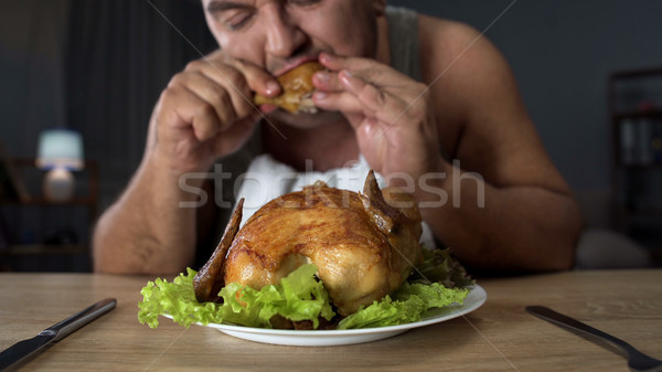 Plump male eating fatty fried chicken hungrily, high-calorie food and addiction Stock photo © motortion