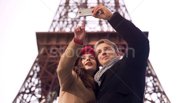 Happy loving couple of tourists doing selfie on background of Eiffel Tower Stock photo © motortion