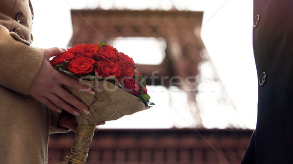 Loving man giving beautiful bouquet of scarlet roses to his sweetheart, love Stock photo © motortion