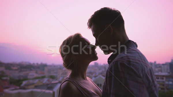 Cute lovers gently hugging, standing on roof, beautiful sunset city background Stock photo © motortion