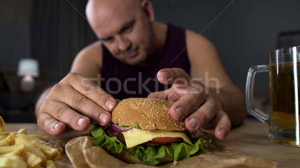 Obese man cooking big burger, overeating gourmet admiring his meal, close-up Stock photo © motortion