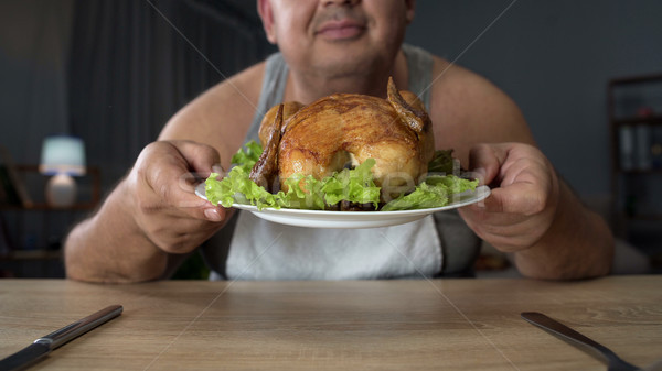 Overweight man smelling greasy grilled chicken with enjoyment, unhealthy food Stock photo © motortion