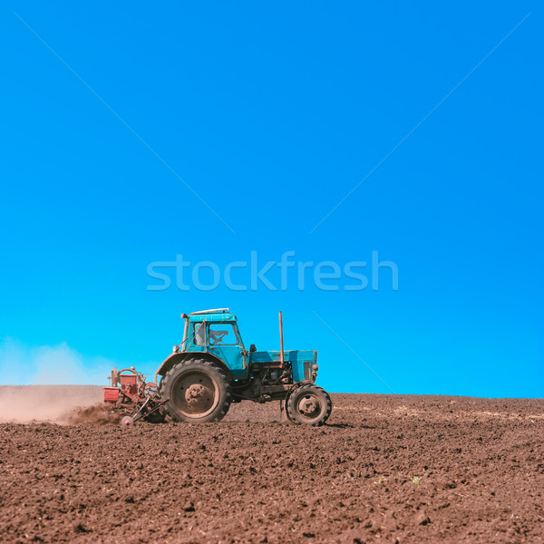 Tractor cultivating field at spring Stock photo © motttive