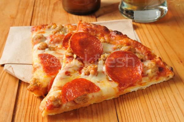 Pepperoni salsiccia pizza fette rustico tavolo in legno Foto d'archivio © MSPhotographic