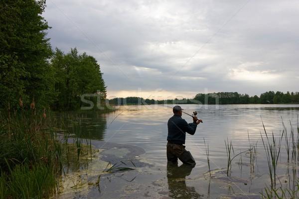 рыбак Постоянный озеро рыбы облачный день Сток-фото © mtmmarek