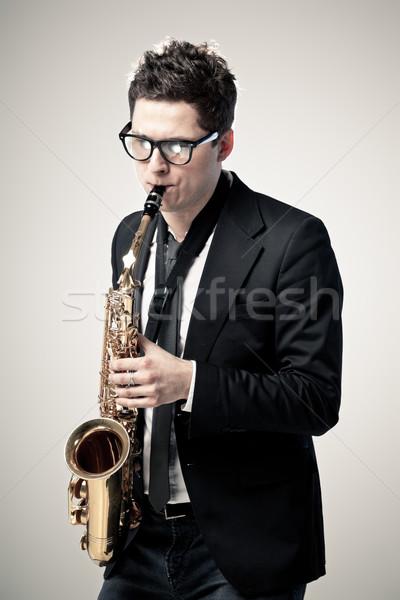Szaxofon fiatalember játszik szaxofon szürke férfi Stock fotó © mtoome