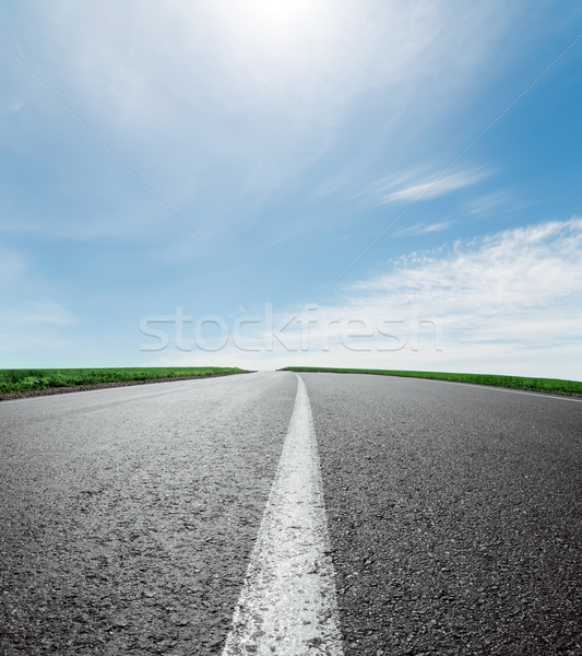 asphalt road to horizon under sky with clouds and sun Stock photo © mycola