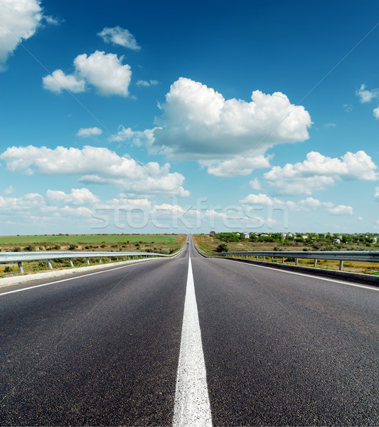 black asphalt road to horizon under deep blue cloudy sky Stock photo © mycola