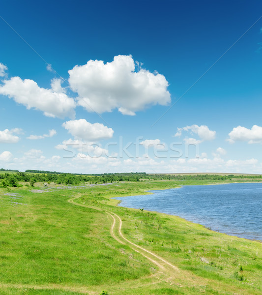 Stock photo: green landscape with road and pond under blue sky with white clo