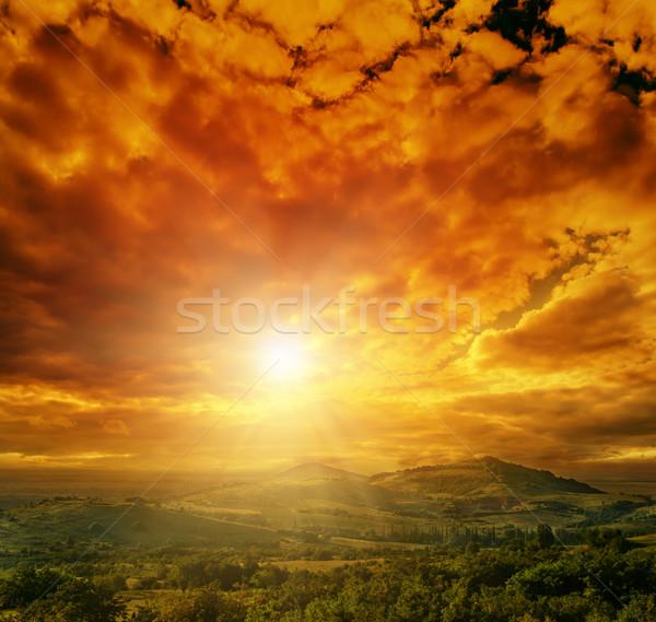 Dramático vermelho céu montanhas árvore pôr do sol Foto stock © mycola