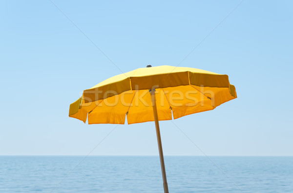 yellow umbrella over sea under blue sky Stock photo © mycola