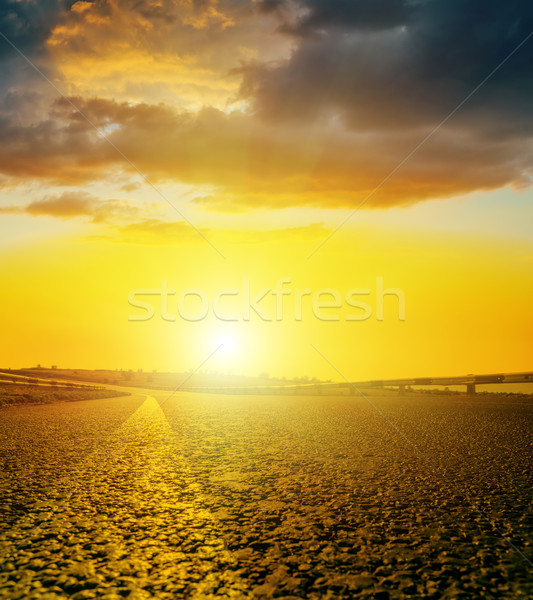 yellow sunset with dark clouds over asphalt road Stock photo © mycola