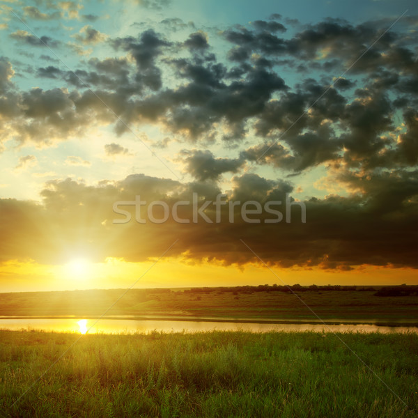 orange sunset with dark clouds over river Stock photo © mycola