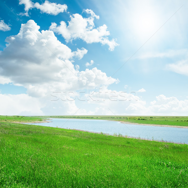 sun in cloudy sky over river with green sides Stock photo © mycola