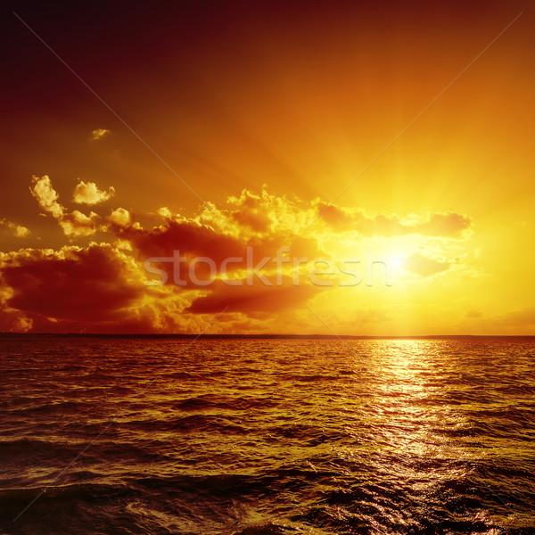 Stock photo: red dramatic sunset over dark water