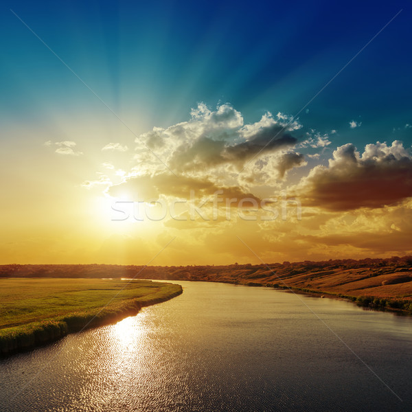 Stock photo: good sunset with rays in clouds over river