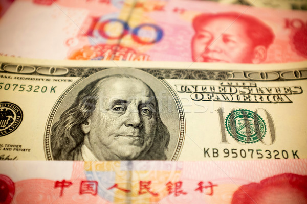 Stock photo: Chinese Yuan Note and U.S. dollar background  (Exchange rate concept)
