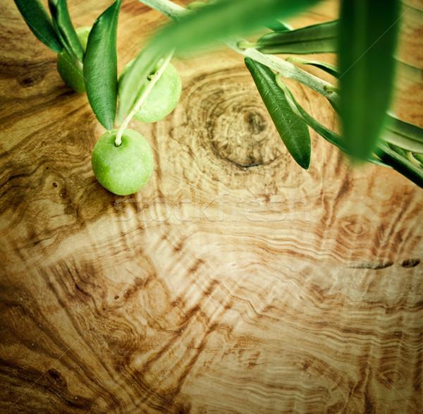Olive branch on olive wood background Stock photo © mythja
