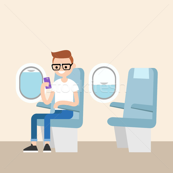 Funny red head nerd sitting on the plane and holding his smart p Stock photo © nadia_snopek