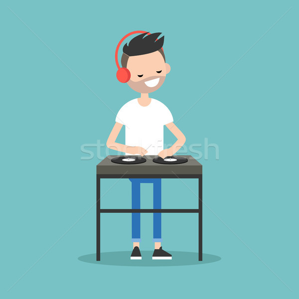 Young bearded DJ wearing headphones and scratching a record on t Stock photo © nadia_snopek