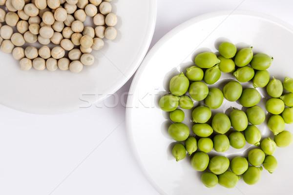 Fresh and dried green peas on plate Stock photo © nailiaschwarz