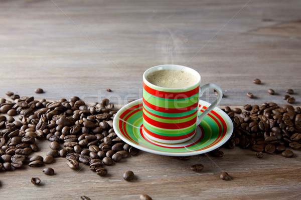 Coffee in striped cup with beans Stock photo © nailiaschwarz