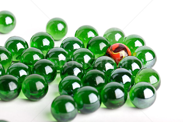 Group of green glass marbles with one orange Stock photo © nailiaschwarz