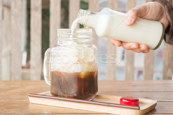 Pouring milk to iced glass of coffee Stock photo © nalinratphi