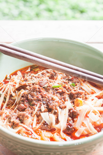 Spicy noodle in meat soup with chopsticks on table Stock photo © nalinratphi