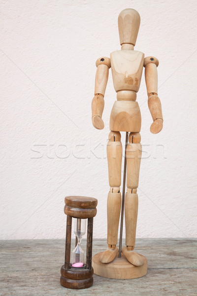 Wood mannequin and hourglass to represent time over  Stock photo © nalinratphi