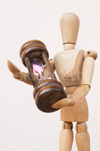 Wood mannequin and hourglass to represent time giving Stock photo © nalinratphi