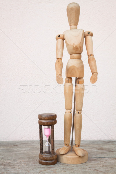 Wood mannequin and hourglass to represent spending time Stock photo © nalinratphi