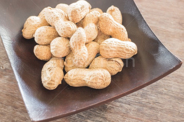 Salted peanuts on wooden bowl Stock photo © nalinratphi