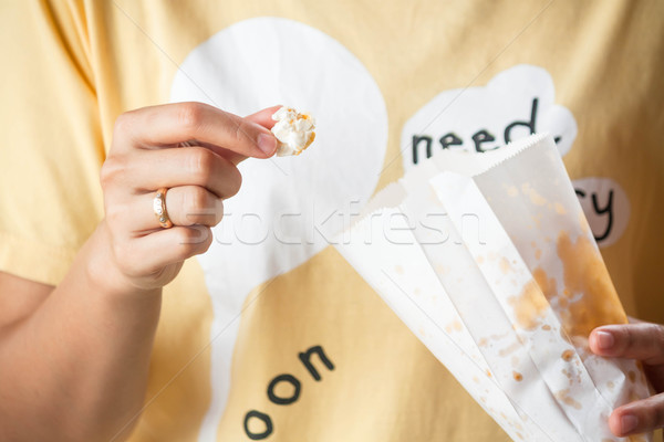 Kobieta jedzenie popcorn torby papierowe żywności tle Zdjęcia stock © nalinratphi