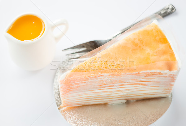Crepe cake with orange sauce on white background Stock photo © nalinratphi