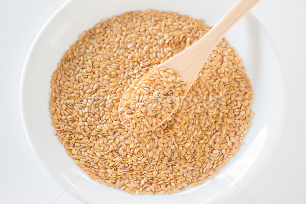 Gold flax seeds on a wooden spoon Stock photo © nalinratphi