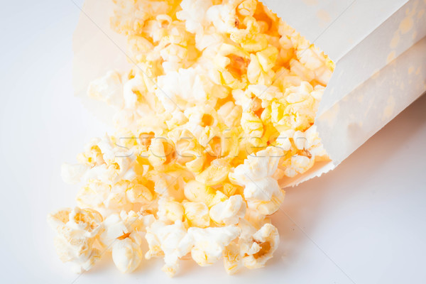 Fresh butter popcorn falling out of paper bag Stock photo © nalinratphi