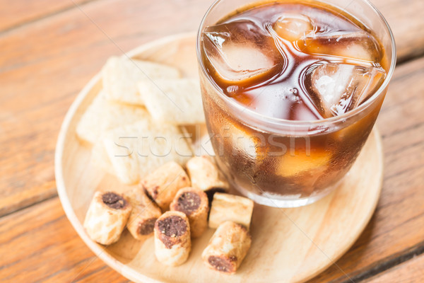 Glass of black iced coffee with some snack Stock photo © nalinratphi