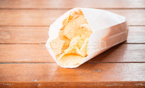 Potato chips in paper bag on wood table  Stock photo © nalinratphi